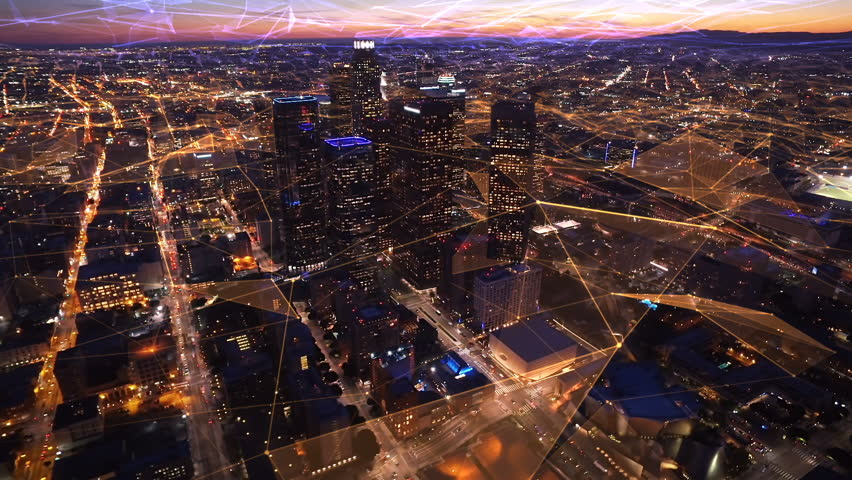 Connected aerial view of the Financial District in Downtown Los Angeles, California.  Sunset. Famous skyscrapers and freeway full of cars. Futuristic. Technology. Shot from helicopter.