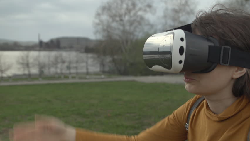An attractive girl in a yellow sweater sits on the grass in a city park and uses virtual reality glasses on a springy cloudy day, close-up shot. | Shutterstock HD Video #26498177