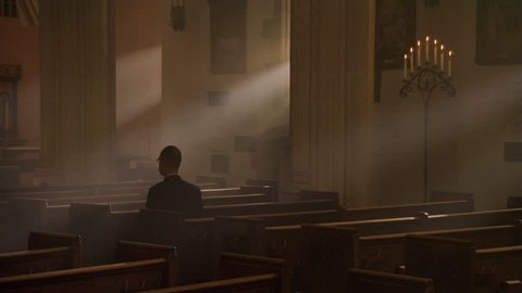 Man kneeling and praying in nave of Catholic church