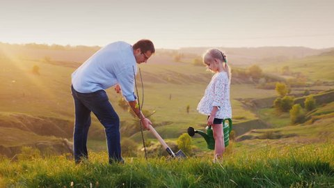 Father and daughter work together. They plant a tree seedling in a picturesque place. The father digs a hole, the daughter holds a watering can and helps him. Strong family, volunteer work