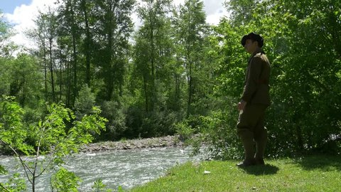 man with old french military uniform, smoking cigarette near the river