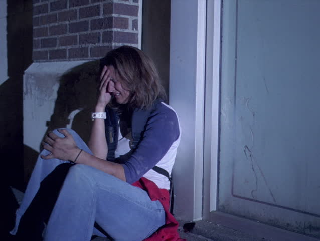 Sobbing teenage girl sitting in a doorway on a lonely street at night | Shutterstock HD Video #26581211