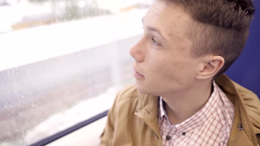Teen boy with pimples on the face going on the train and looking out the window. Closeup.   Shutterstock HD Video #26609357
