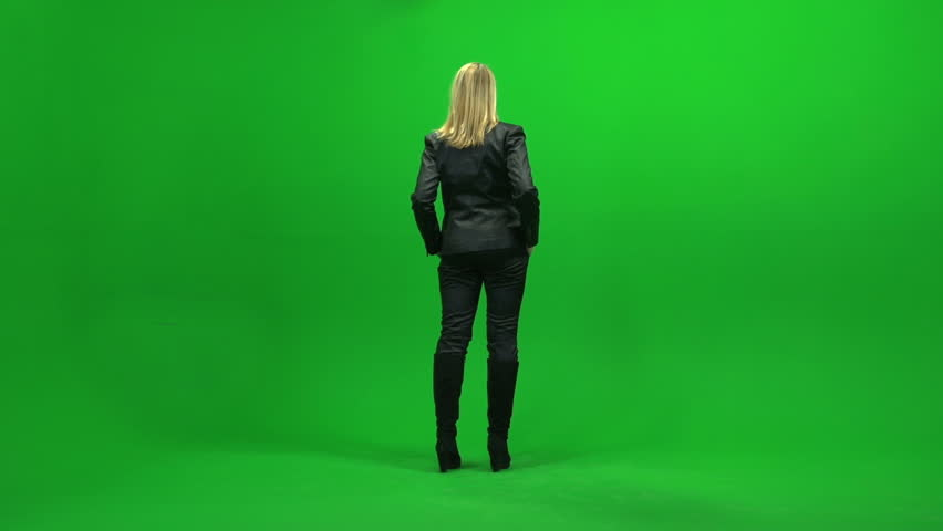 full body shot of young women standing isolated against green screen background. one person looking arround in room. female model scene
