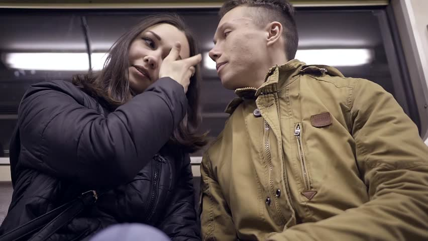 Young couple the girl in a warm black jacket and boy in winter jacket brown sitting in a subway car and gently touching the face each other to communicate | Shutterstock HD Video #26621647