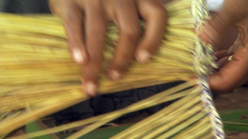 Close-up of Fijian woman's hands as she makes a broom from palm fronds