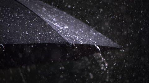 Close-up ultra-slow motion rain falling on a black umbrella