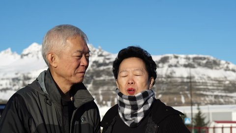 Cute Asian senior couple happy honeymoon anniversary trip in Europe snow alp. Kissing on cheek