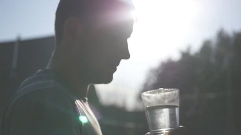 A young man drinks clean water from a glass, drops of water flow along the bottom and shine in the rays of the sun. Slow mothion. Full HD 1920x1080p