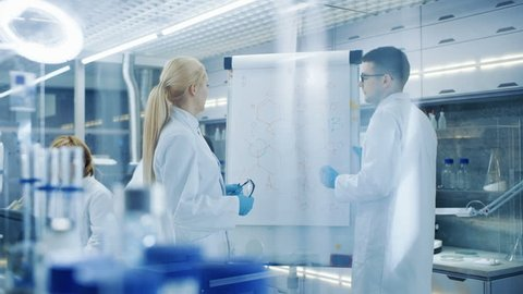 Young Female and Male Scientists Write Formulas on a Whiteboard. They're Solving Scientific Problems in Bright Modern High Tech Laboratory. Shot on RED EPIC-W 8K Helium Cinema Camera.