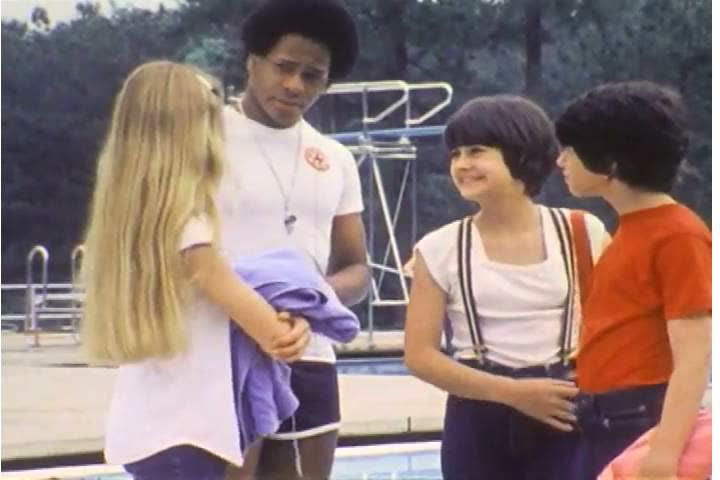 1970s: A group of adolescent kids swim at public pool, and a girl talks about a crush she has on a lifeguard in the 1970s. | Shutterstock HD Video #26742163