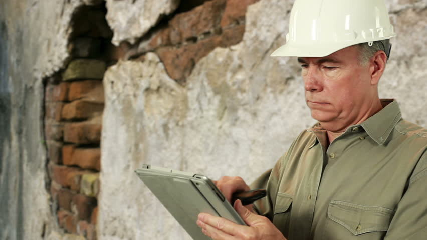 Man in hardhat with old brick wall in background engaged in cell phone conversation while using electronic tablet.