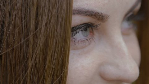 Close up of eye view of the girl with auburn hair looking at camera and smiling