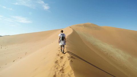 Tourist walking on the scenic dunes of Sossusvlei, Namib desert, Namib Naukluft National Park, Namibia. Afternoon light. Adventure and exploration in Africa. Slow motion.