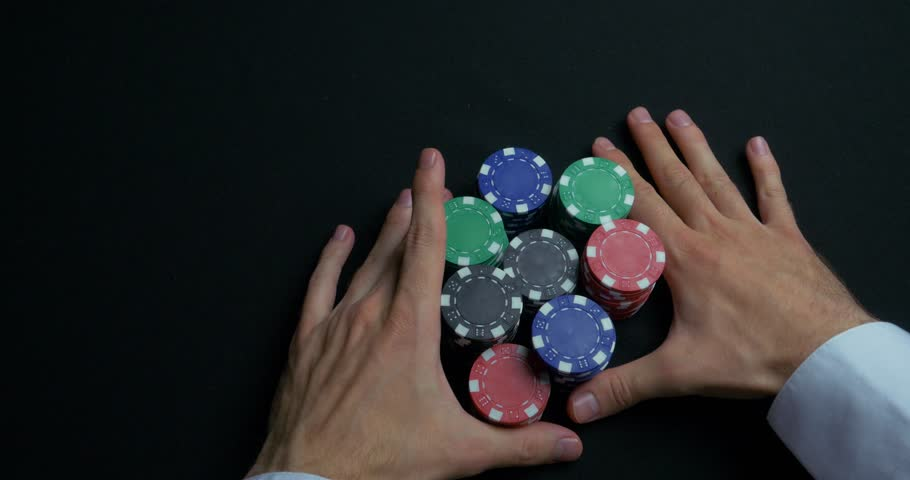 Stack of poker chips and two hands on table. Closeup of poker chips in stacks on green felt card table surface. Poker chips and hands above it on green table. Dealer