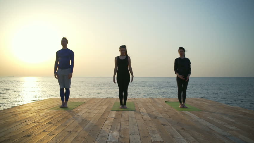 Three persons meditating on the wooden terrace slow motion | Shutterstock HD Video #26775517