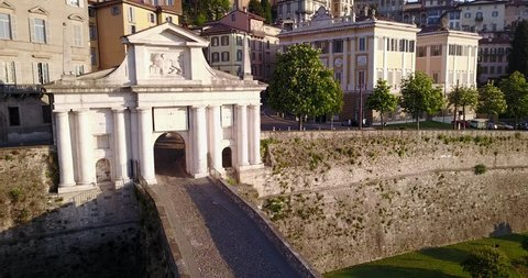 Bergamo - Old city. One of the beautiful city in Italy. Aerial footage of the old gate named Porta San Giacomo during the sunrise and a wonderful blu day