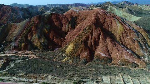 Flying a drone over the colorful Zhangye Rainbow Mountains; aerial view on sandstone hills and mountain chains covered by amazing pattern. Part 1 of a continuous 5 part series.