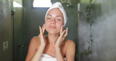 Woman Applying Skincare Lotion To Face Caring For Skin In Bathroom Beautiful Girl In Towel Happy Smiling Doing Morning Hygiene Point Of View Slow Motion 60