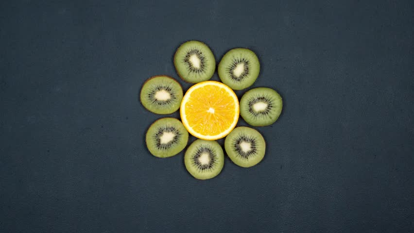 a Flower Made of Fruits. Dance of Oranges And Kiwi. Fruits on a Black Background. Stop a Motion Animation With Citrus. Top View. 4K.