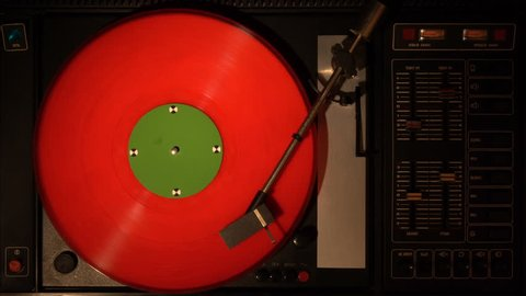 Vinyl record player. Plays song from an old turntable, 4k top view. Black background. Music round plate rotates.Music disc turns. Tracking shot rotating disk with chroma-key green screen. Tracking point.