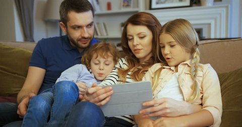 Mother, father, son and daughter using tablet, watching movie. Family spending time together at home. Happy family