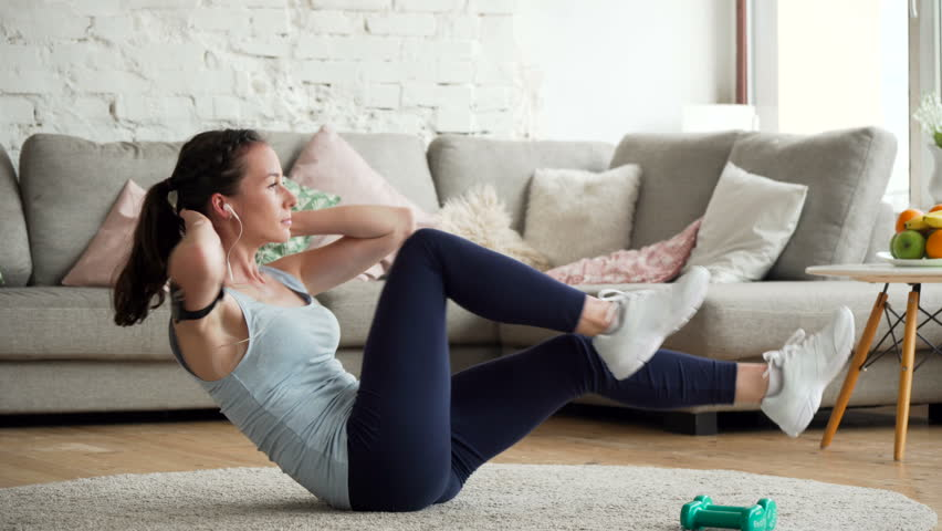 young fit and tone up woman doing fitness workout and sit ups exercises for health using app on mobile phone fixed on hand to listen music in living room at home during sunny day
