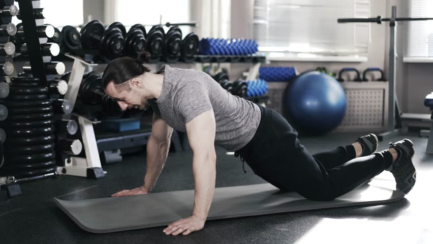 Side view of a young muscular man in a gray t shirt doing push ups on his knees in a gym. Locked down real time medium shot | Shutterstock HD Video #26870587