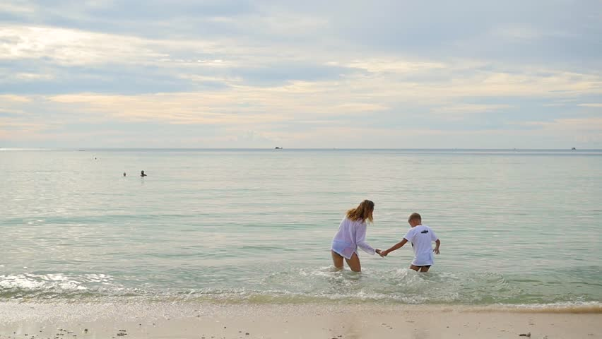 Happy family holding hands running along the shore. To run in the water creating splashes