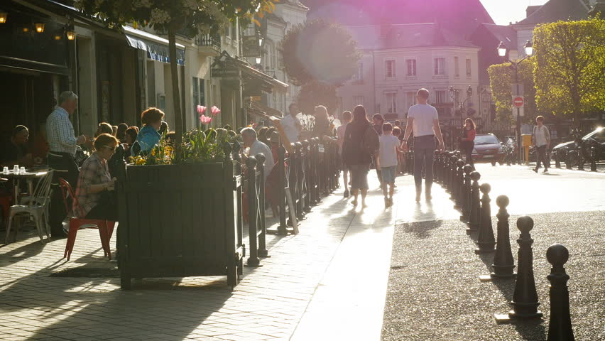 AMBOISE, FRANCE - CIRCA 2017: Place Michel Debre in central Amboise restaurants cafe bars full people tourist travelers majestic Amboise Chateau Castle left hand with cinematic sunset flare at sunset