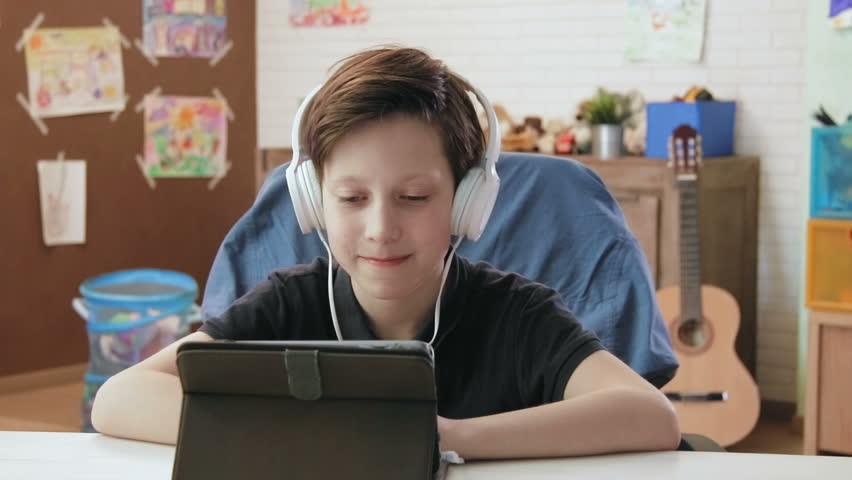 Cute little boy watching funny videos using digital tablet, wearing headphones | Shutterstock HD Video #26878657