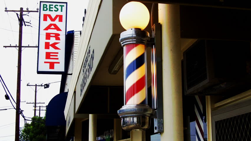 LONG BEACH, CA/USA- August 12 2012: A barber pole and family market sign evoke the struggle of small businesses to stay open in the face of competition from mega stores circa 2012 in Long Beach CA.