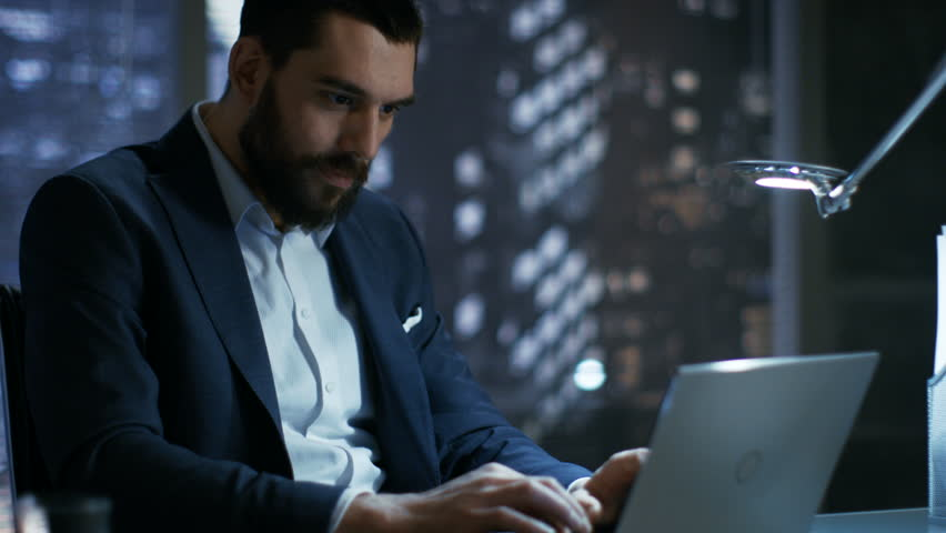 Late at Night in Private Office Businessman Works on a Laptop. He Succeeded Internationally by Winning Big Contract. He's Very Happy.  | Shutterstock HD Video #26897107