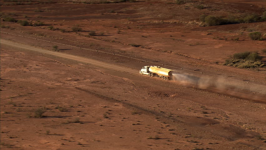 Aerial view of a tanker truck watering a red dirt road west of Alice Springs, Australia