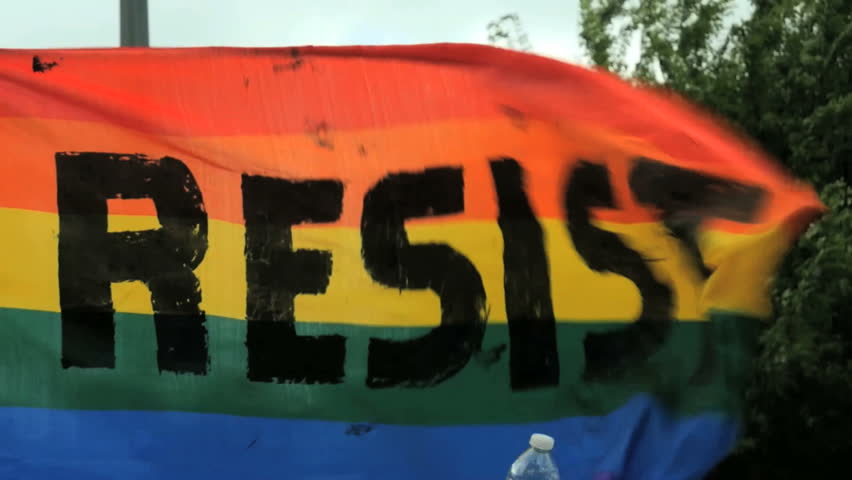 Resist sign banner Rainbow flag waves in the wind blowing during activist rally gathering.  Activism slow motion LGBTQ gay pride civil rights climate march