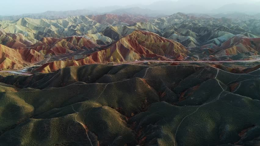 Approaching one of the most beautiful rainbow mountains in Zhangye National Geopark, part 3 of a continuous 3 part series. Aerial view on grass-covered sandstone hills in front of a colorful mountain