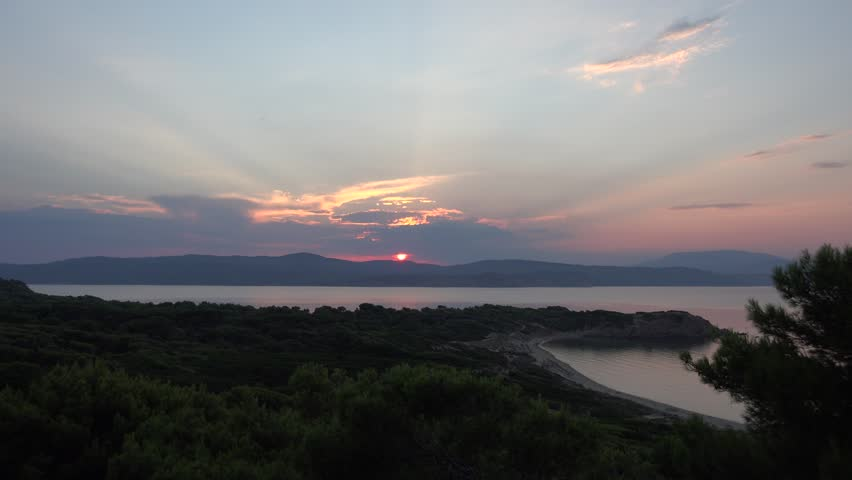 4K Aerial view of amazing sunset over forest tree and seascape, Skiathos Island emblem
