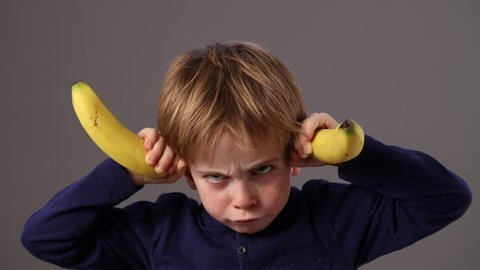 aggressive little preschool boy making a statement, threatening like a bully with a dirty look and two bananas as horns expressing his frustration, disagreement or anger, grey background studio
