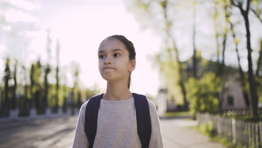 Child girl is walking with a school bag in sunny day. Steadicam shot, front view, 4K