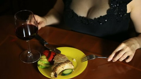 A close-up of a woman with a neckline cuts a piece of cutlets into bones cooked on a grill. Sexy woman eating meat and drinking wine