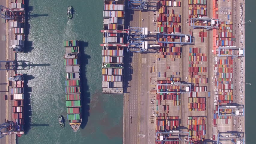 Aerial time lapse of a Commercial port with container ships during loading and unloading, and a container ship pulled by tugboats - Top down aerial view.