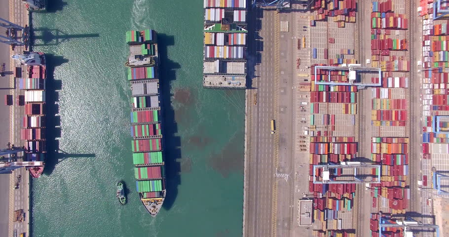 Commercial port with container ships during loading and unloading, and a container ship pulled by tugboats - Top down aerial view. | Shutterstock HD Video #26983690