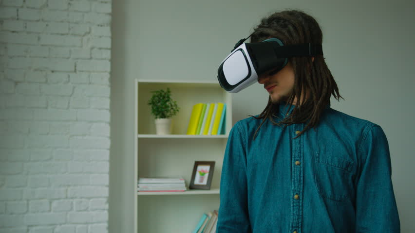 098ff6b77c7b Young hipster man with dreadlocks using virtual reality headset and playing  games at home. Vr glasses.