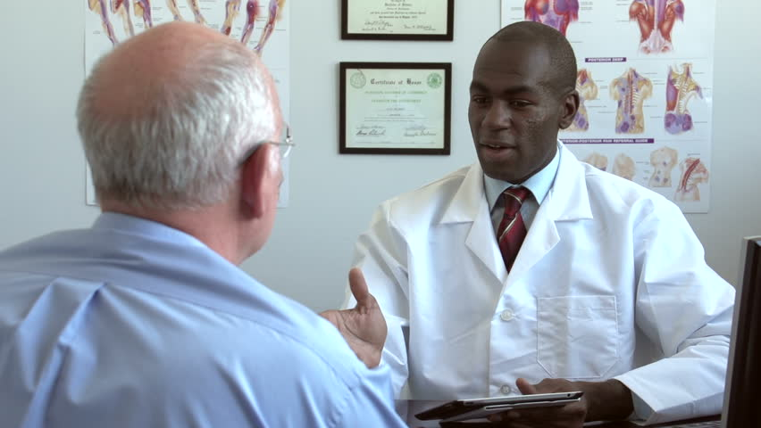 Doctor meeting with patient, using tablet