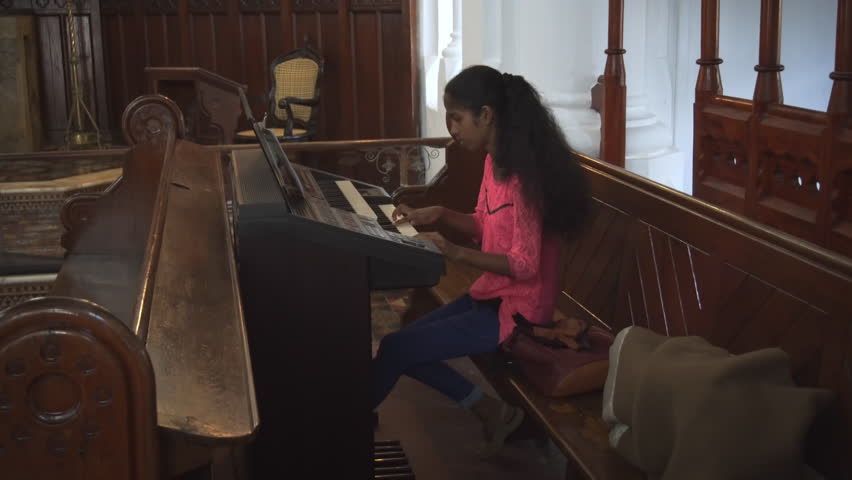 GALLE. SRI LANKA - CIRCA DEC 2016: Local girl plays on an electronic organ inside the historic Dutch Reformed Church in Galle. 4k UHD stock video | Shutterstock HD Video #27012667