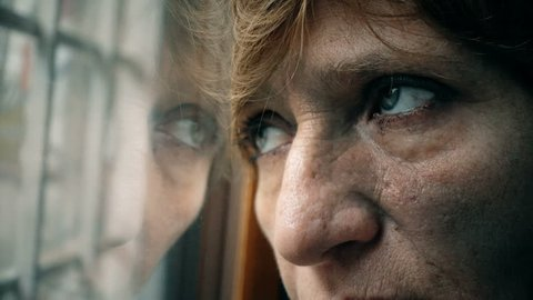 Wrinkled Eyes of sad, depressed mature woman looking out the window