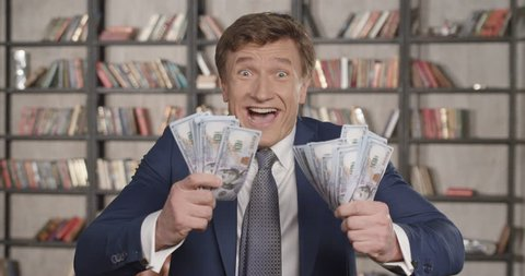 Great Winning! Slow Motion Portrait of Very Happy Successful Cheering Man Throwing Money Up, Rising Hands Celebrating His Successful Win With a Lot of Dollars. Businessman Series. 4K UHD 4096x2160.