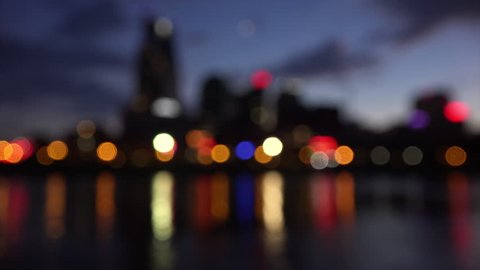 Blurred downtown Nashville, Tennessee city skyline across the Cumberland River at night
