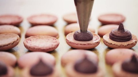 cooking, food and baking concept - confectionery bag or injector squeezing cream filling to macarons shells at pastry shop