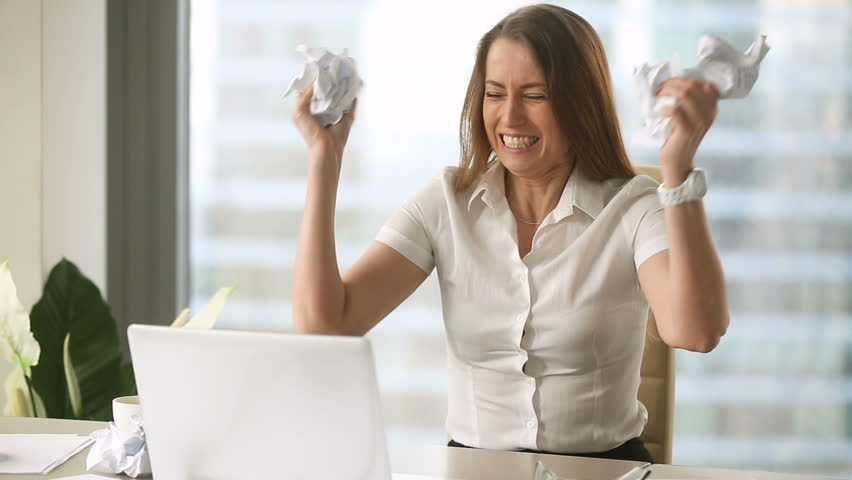 Angry furious female office worker throwing crumpled paper, having nervous breakdown at work, screaming in anger, stress management, mental distress problems, losing temper, reaction on failure